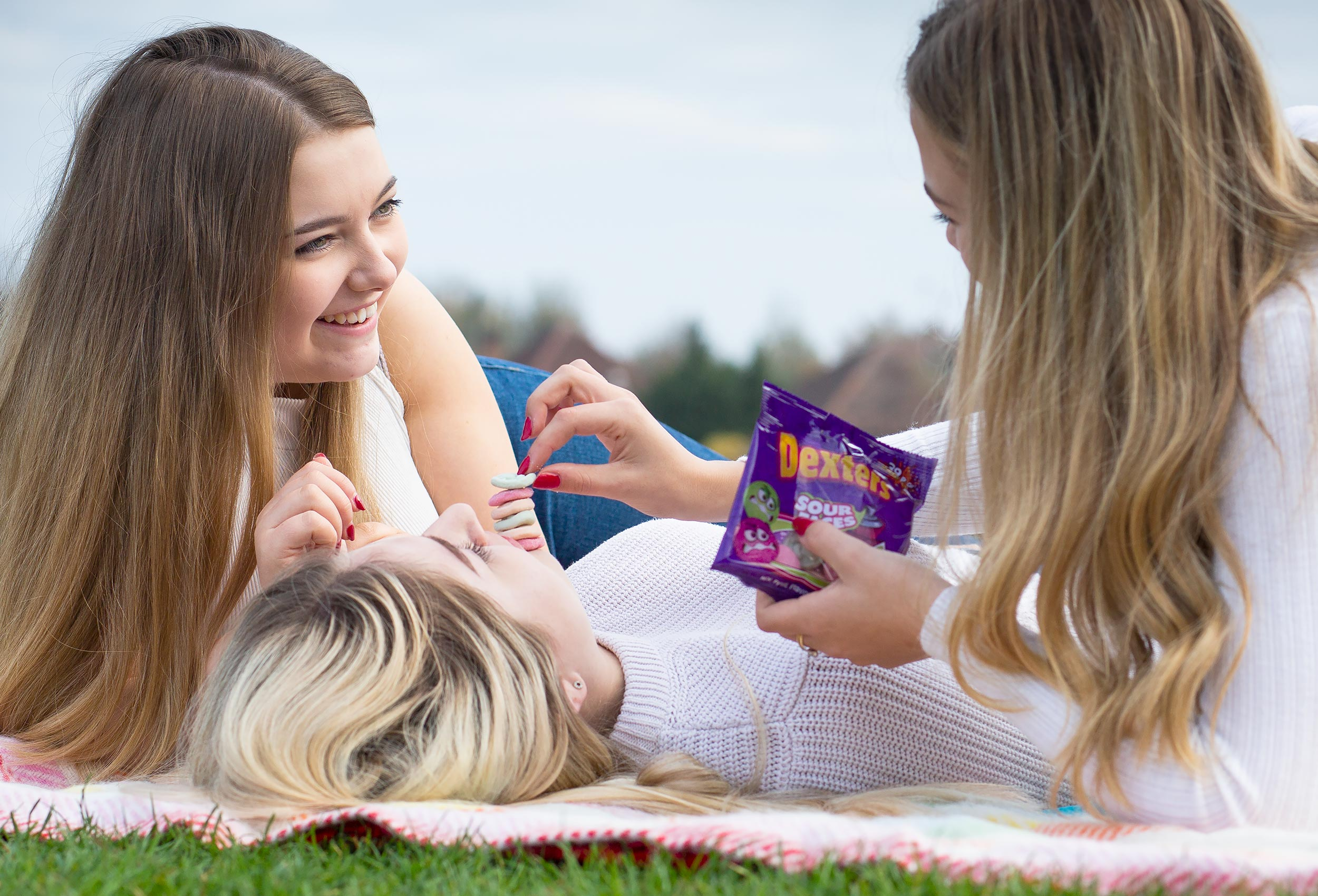 Commercial photography of friends on a picnic rug in a Leicestershire park balancing sweets on each other.