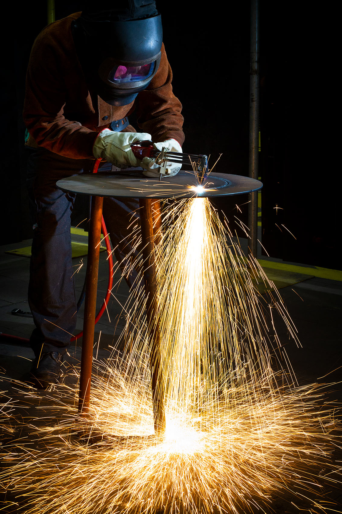 Sparks flying as Cadent Gas engineer cuts metal with a welding torch in Birmingham workshop