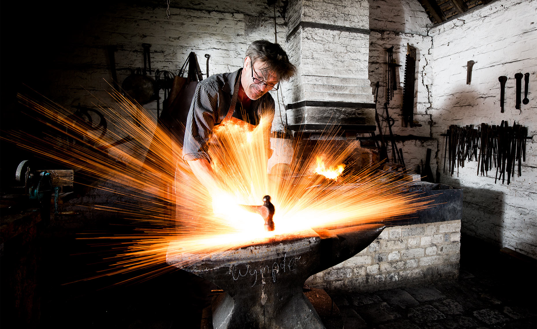 Editorial feature photography of Simon Damant at work the forge on the Wimpole Estate, Cambridgeshire.