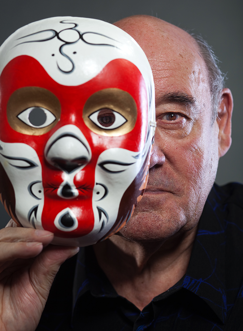 Editorial studio portrait of Dr Desmond Morris with a tribal mask.