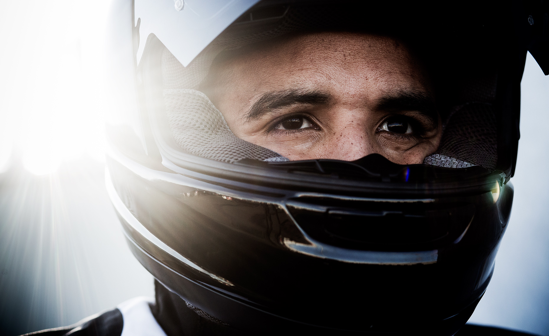 Close up editorial portrait of Andrew Shim in a motorcycle helmet.