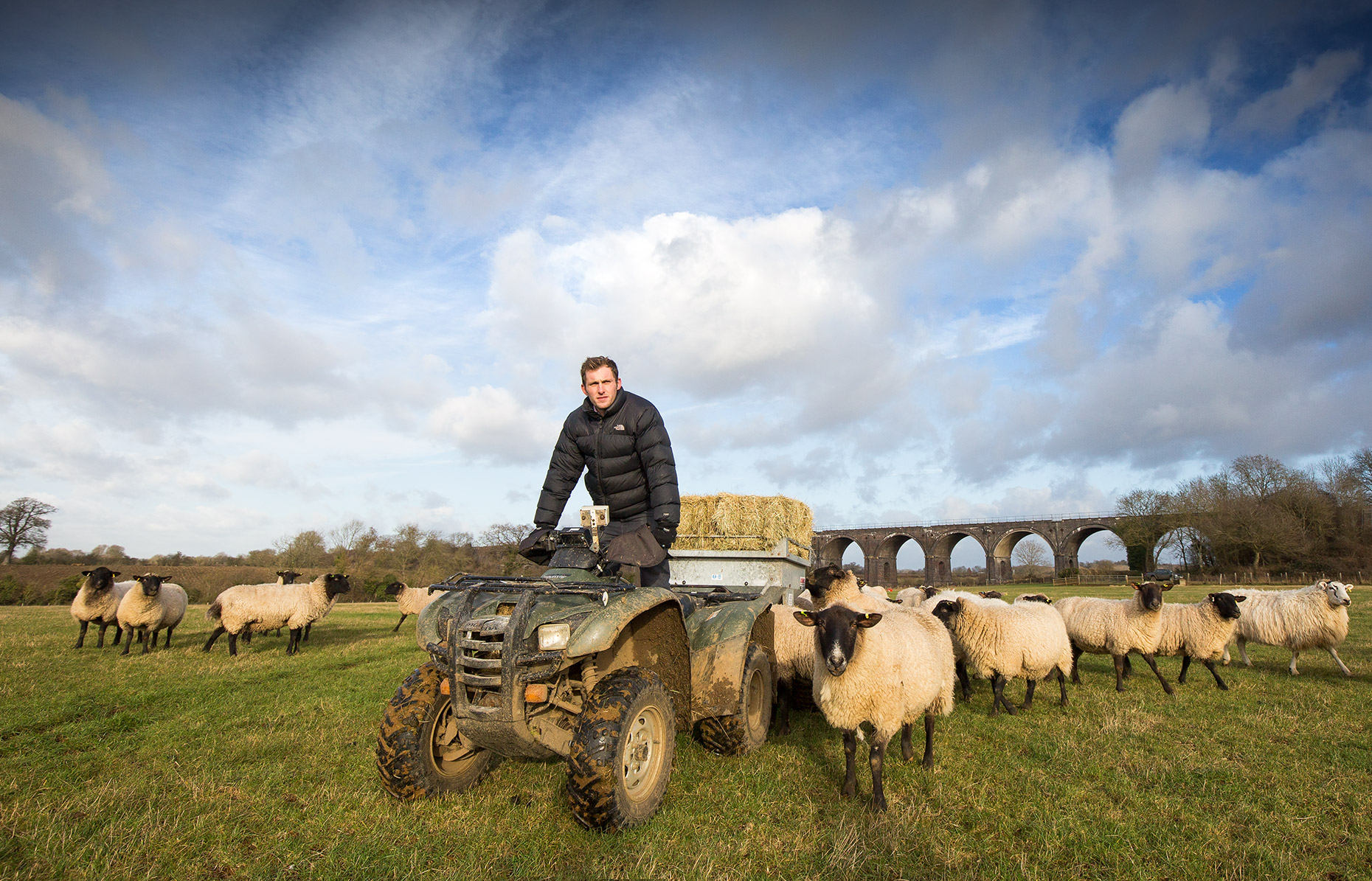 Editorial feature photography of a farmer on a quad bike taking feed to his sheep.